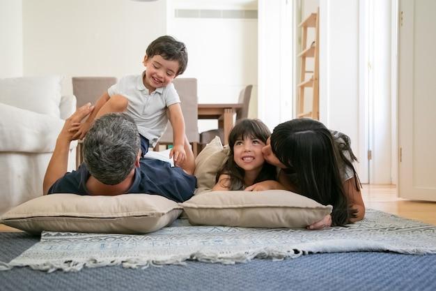 うれしそうな面白い親が寄り添い、抱き合ったり、小さな子供にキスしたり、一緒に楽しんだり 無料写真