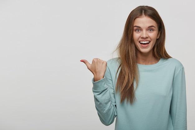 彼女の親指で空のコピースペースを示すうれしそうな面白い10代女性 無料写真