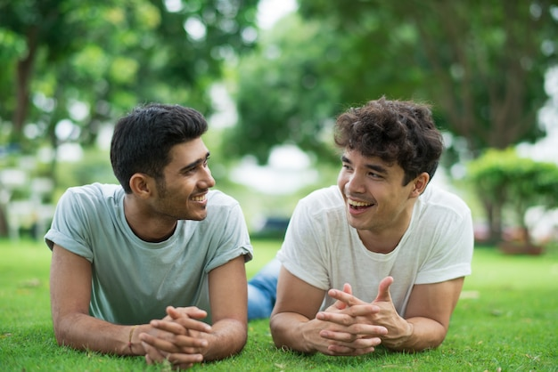 Joyful gays chatting and laughing while lying on grass Free Photo
