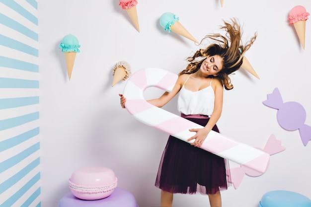 巻き髪を振って目を閉じて踊っているうれしそうな女の子はピンクのキャンディの杖を保持しています。お菓子で飾られたテーマパーティーで楽しんで、壁でポーズの魅力的なドレスの魅力的な若い女性 無料写真