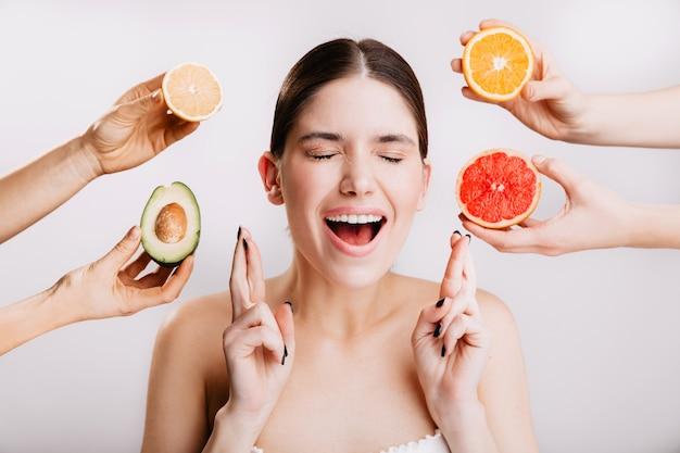 La ragazza allegra esprime il desiderio. ritratto di modello senza trucco sul muro bianco con frutti. Foto Gratuite