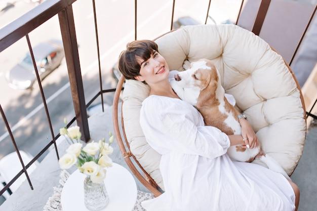 Gioiosa ragazza seduta in poltrona accanto a un vaso di rose bianche e accarezzando il cane beagle. bella donna dai capelli castani che gode dell'aria fresca sul balcone con l'animale domestico si trova sulle sue ginocchia Foto Gratuite