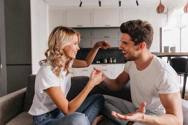 家で遊んでいる間、彼氏の気をそらそうとしているうれしそうな女の子。面白い男はゲーム中に彼のガールフレンドと議論します。 無料写真
