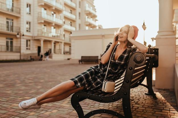 Ragazza allegra in scarpe da ginnastica bianche che si siede sulla panchina in serata. foto all'aperto di incredibile signora bruna parlando al telefono per strada. Foto Gratuite
