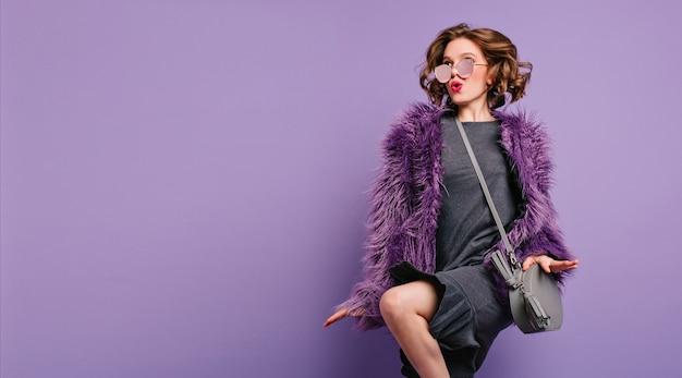 キスの表情と紫色の背景で踊る巻き毛の茶色の髪のうれしそうな女の子 無料写真