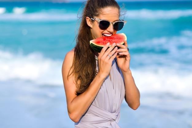 スイカをかむ長い薄茶髪のうれしそうな女の子。笑顔で好きな食べ物を楽しんでいる大きな暗いサングラスで興奮した女性モデルのクローズアップの肖像画。 無料写真