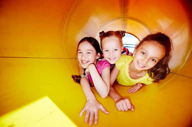 Joyful girls sliding down slide Free Photo