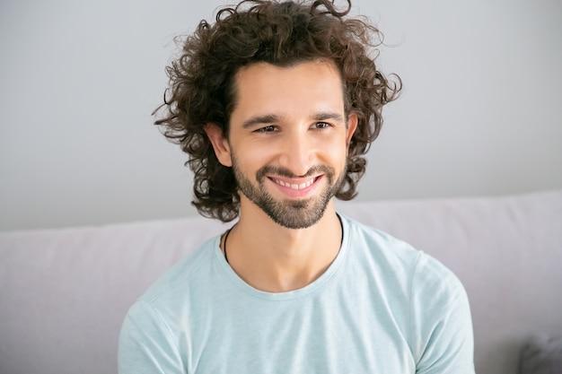 캐주얼 티셔츠를 입고 집에서 소파에 앉아 멀리보고 웃고 웃고 즐거운 잘 생긴 곱슬 머리 남자. 남성 초상화 개념 무료 사진