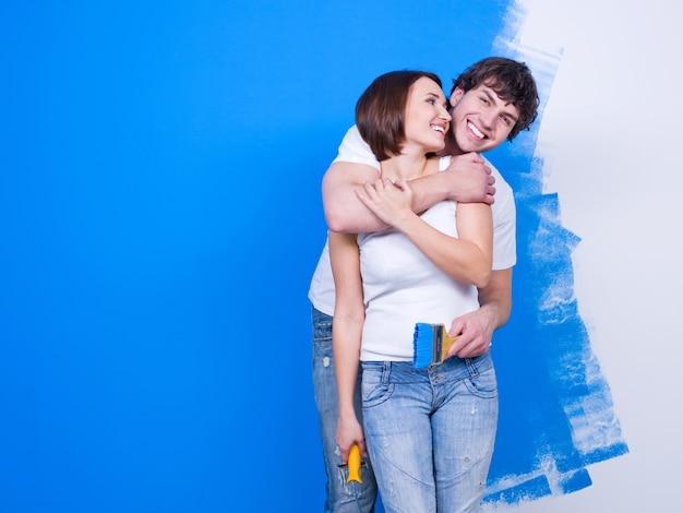 Gioiosa coppia di innamorati abbracciando felice in piedi vicino al muro dipinto Foto Gratuite