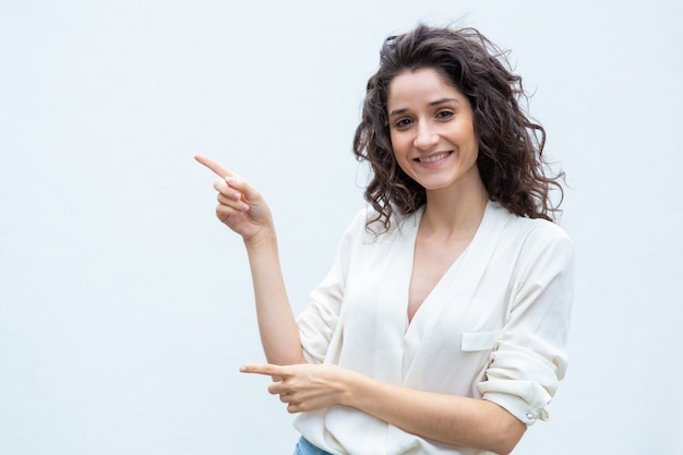 Joyful happy female customer pointing fingers away Free Photo