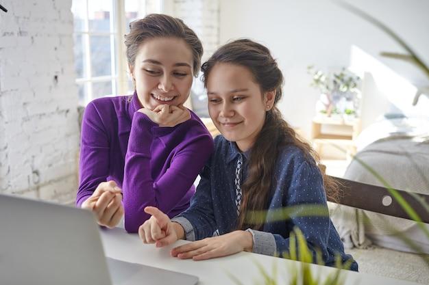 Радостная счастливая молодая мать и дочь делают покупки в интернете с помощью портативного компьютера, сидя за столом в светлом интерьере спальни, указывая пальцами на экран и улыбаясь Бесплатные Фотографии