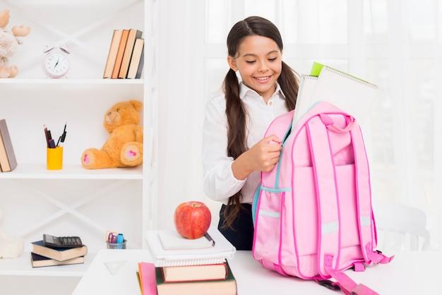 Joyful hispanic schoolgirl packing schoolbag Free Photo