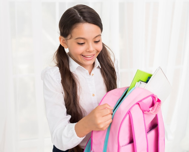 Joyful hispanic schoolgirl zipping up school bag Free Photo