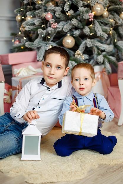 Радостные дети открывают рождественские подарки. уютный теплый зимний вечер. семья в канун рождества. дети под елкой с подарочными коробками. украшенная гостиная. милые дети с рождественскими подарочными коробками дома. Premium Фотографии