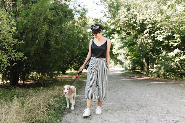 Joyful lady in white sneakers walking with beagle dog in park in sunny day, enjoying good weather Free Photo