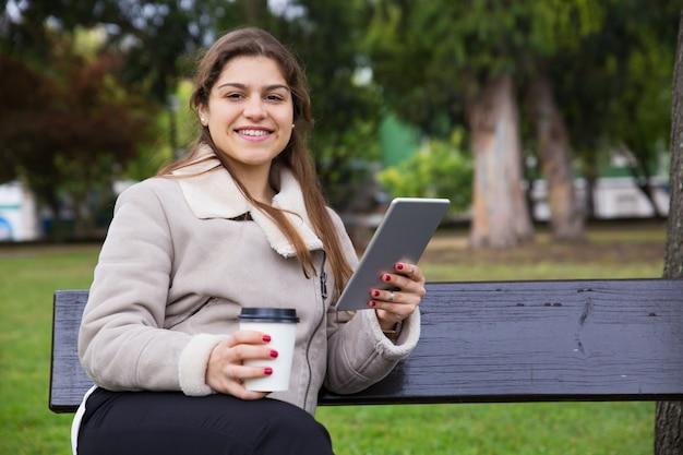Joyful latin college girl with tablet drinking takeaway coffee Free Photo