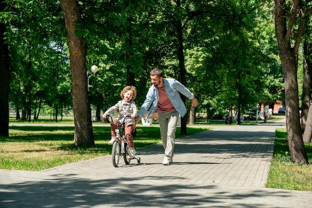 夏の公園で緑の芝生と木々に囲まれた道路に沿って近くを走っている父親と一緒に自転車に乗っているうれしそうな男の子 Premium写真