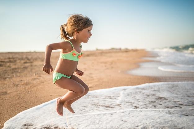 즐거운 어린 소녀는 화창한 따뜻한 여름날에 바다에서 휴식을 취하면서 해변의 날을 즐깁니다. 프리미엄 사진