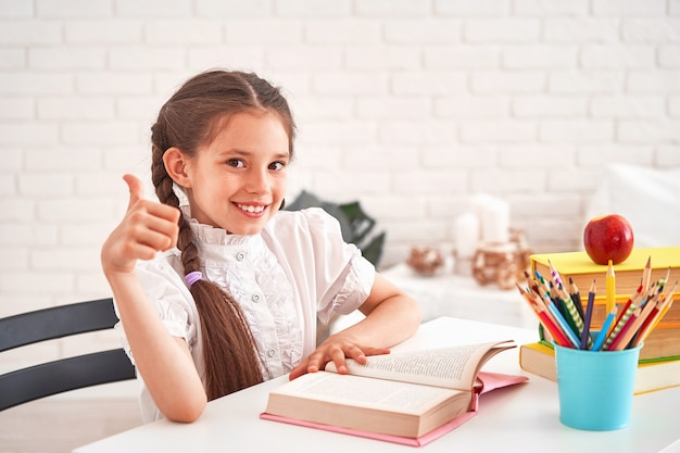 Joyful little girl sitting at the table with pencils Premium Photo