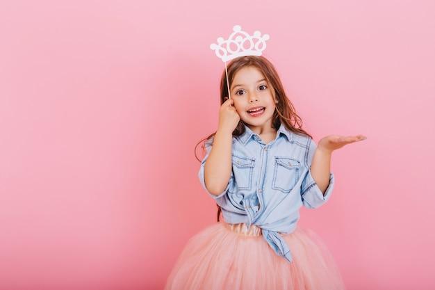 ピンクの背景に分離された頭の上の王女の王冠を保持しているチュールスカートで長いブルネットの髪を持つうれしそうな少女。キッズのための明るいカーニバルを祝い、誕生日パーティーの積極性を表現 無料写真