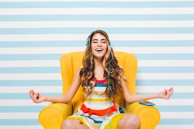 Радостная длинноволосая девушка медитирует, сидя в позе лотоса на синей полосатой стене. довольно молодая женщина в красочном платье охлаждает в желтом кресле и слушает расслабляющую музыку. Бесплатные Фотографии
