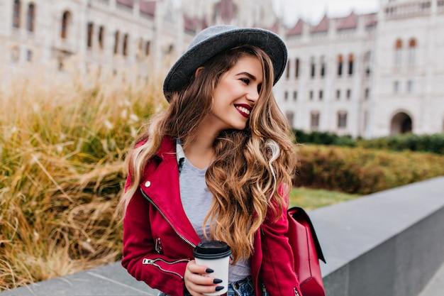 오래 된 건물 근처에서 누군가를 기다리는 동안 멀리보고 유행 검은 매니큐어와 즐거운 긴 머리 여자 무료 사진