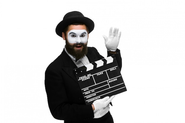 Joyful man in the image mime with movie board Free Photo