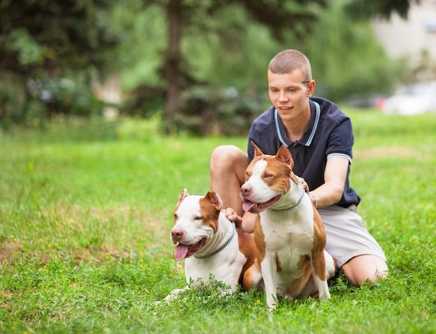 Радостный человек, сидящий на траве с собаками. Premium Фотографии