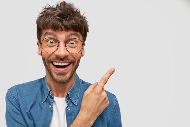Веселый мужчина с широкой улыбкой, с забавным выражением лица, показывает в сторону, рекламирует что-то удивительное. Бесплатные Фотографии