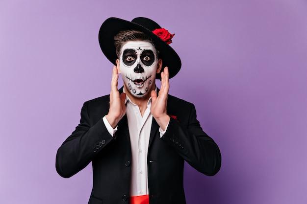 ショックでハロウィーンの化粧をしているうれしそうな男は、紫色の背景にポーズをとって、カメラをのぞきます。 無料写真