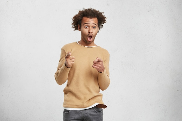 Joyful mixed race man wears sweater, points finger at camera, chooses you, opens mouth widely Free Photo
