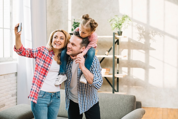 Joyful mother taking selfie on mobile phone while father carrying their daughter on shoulder in living room Free Photo