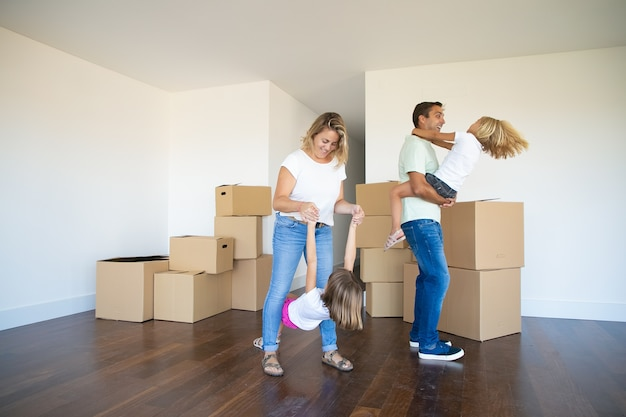 Радостные родители и дети наслаждаются новым домом, танцуют и веселятся возле кучи коробок в пустой комнате Бесплатные Фотографии