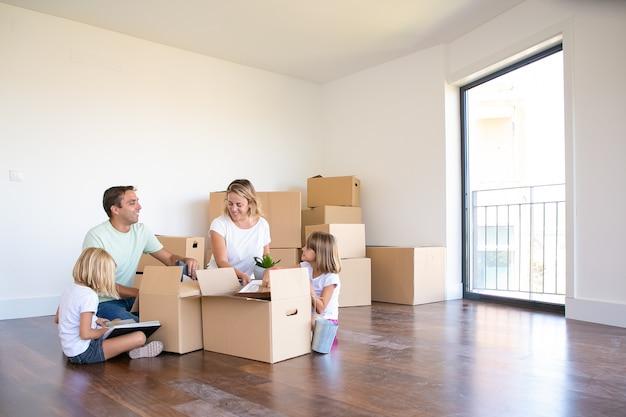 うれしそうな両親と2人の子供が新しい空のアパートで物を開梱し、床に座って開いた箱から物を取り出します 無料写真