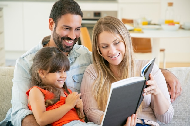 Genitori gioiosi coppia e piccola ragazza dai capelli neri che si siede sul divano in soggiorno, leggendo il libro insieme e ridendo. Foto Gratuite