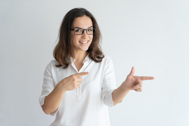 Joyful positive girl in glasses recommending new product or service. Free Photo
