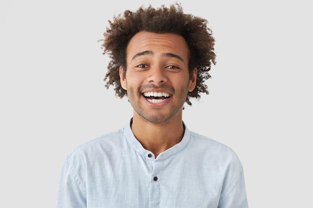 Радостный позитивный мужчина с красивым смехом, широко улыбается или хихикает, чувствует себя прекрасно и в восторге Бесплатные Фотографии