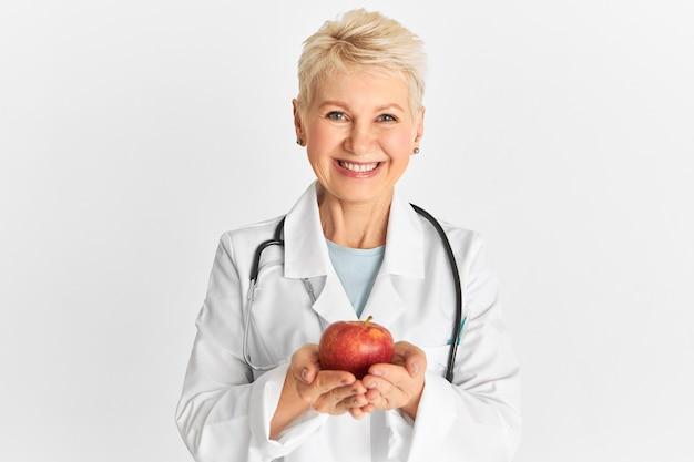 Радостная и позитивная зрелая практикующая женщина держит в руках сладкие хрустящие фрукты, богатые клетчаткой, фитонутриентами и антиоксидантами, и рекомендует есть здоровую органическую пищу. яблоко в день держит доктора подальше Бесплатные Фотографии