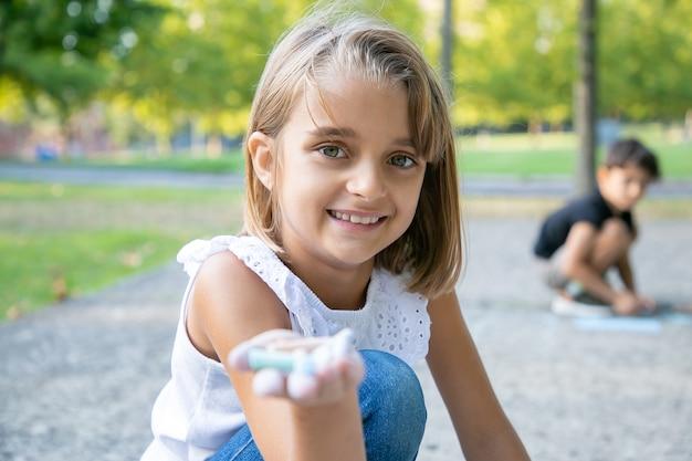 カラフルなチョークを手に持って、コンクリートの上に座って描いているうれしそうなかわいい女の子。クローズアップショット。子供の頃と創造性の概念 無料写真
