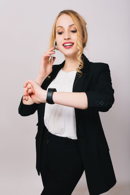 Joyful pretty young businesswoman in office suit talking on phone, smiling and looking at watch. cheerful mood, happy, successful, worker, isolated, corporate Free Photo