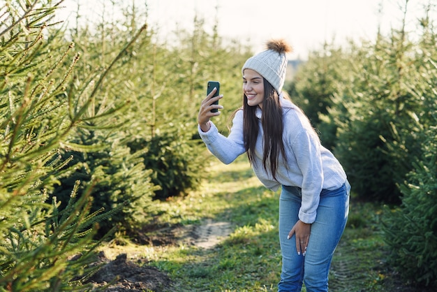 따뜻한 모자 사진에 즐거운 예쁜 젊은 여자 임업 재배 사이 산책하는 동안 아름 다운 크리스마스 트리. 프리미엄 사진
