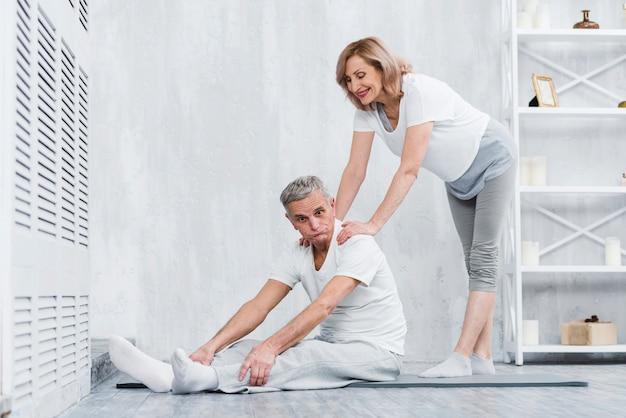 Joyful senior couple making fun while exercising at home Free Photo