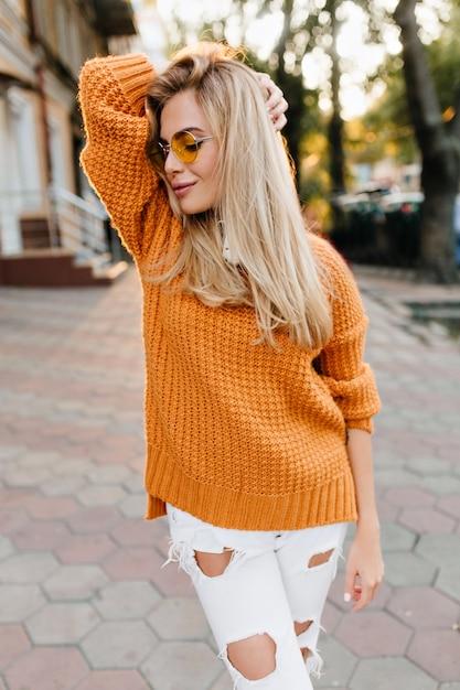 Donna esile allegra in cardigan lavorato a maglia piacevole che gode del tempo libero all'aperto e sorridente Foto Gratuite