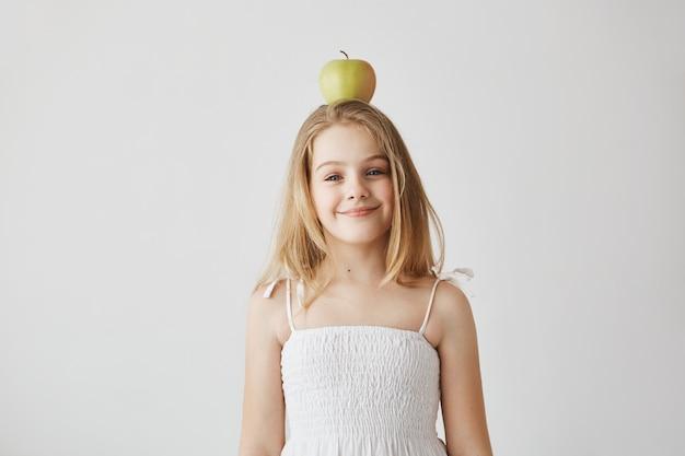 Piccola ragazza bionda allegra con gli occhi azzurri e il sorriso piacevole nella posa divertente del vestito bianco con la mela sulla sua testa per l'archivio di video della famiglia. momenti felici di vita. Foto Gratuite