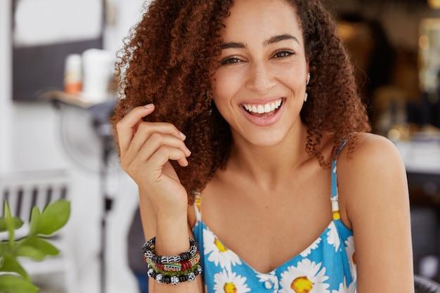 Радостная улыбающаяся темнокожая женщина с густой прической носит летнюю футболку и браслет Бесплатные Фотографии