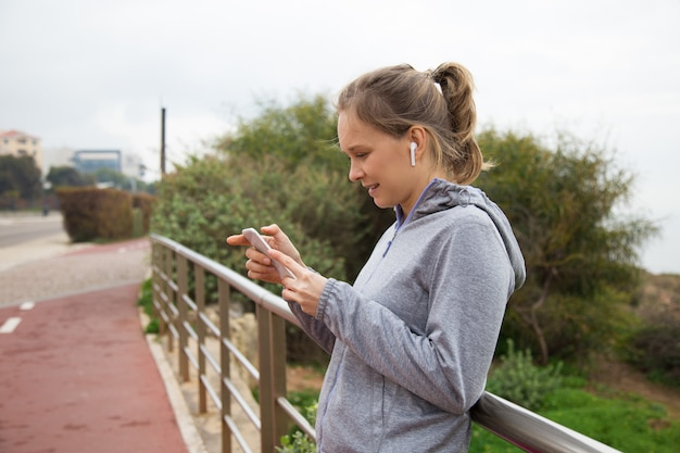 Joyful sporty girl stop jogging and checking up app Free Photo