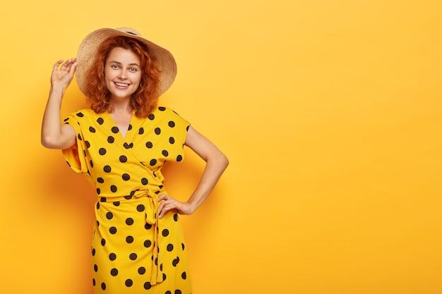 즐거운 여름 아가씨는 허리에 한 손을 잡고 밀짚 모자를 쓰고 생생한 노란색 폴카 도트 드레스를 입고 행복한 표정, 날씬한 몸매, 실내 모델, 프로모션에 적합한 복사 공간을 가지고 있습니다. 아름다움과 여성 무료 사진