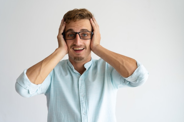 Joyful surprised guy in glasses learning great amazing news. Free Photo