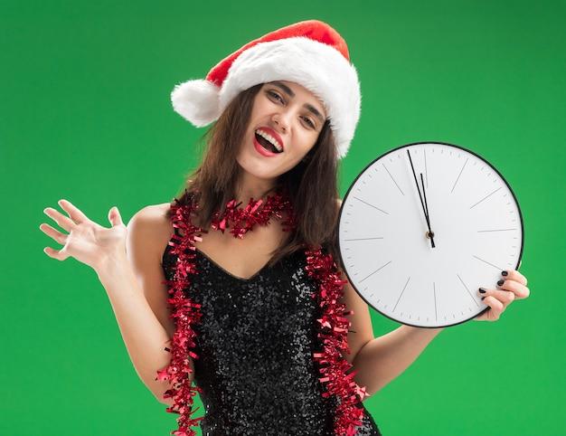 Gioiosa testa inclinabile giovane bella ragazza che indossa il cappello di natale con la ghirlanda sul collo che tiene l'orologio da parete diffondendo la mano isolata sulla parete verde Foto Gratuite