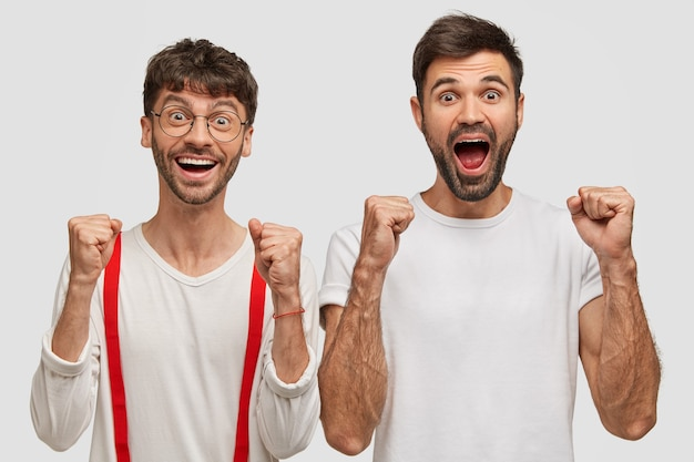 Joyful unshaven two young men clench fists and shout with happiness, dressed casually, isolated on white wall Free Photo
